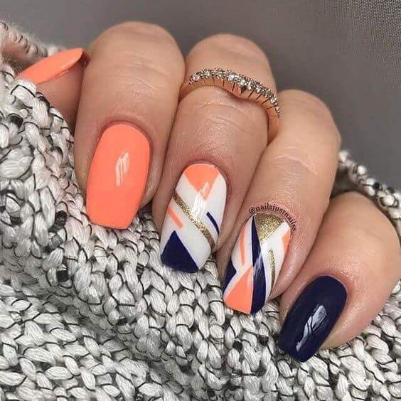 Uñas de colores naranjas, azules, blancas y dorados