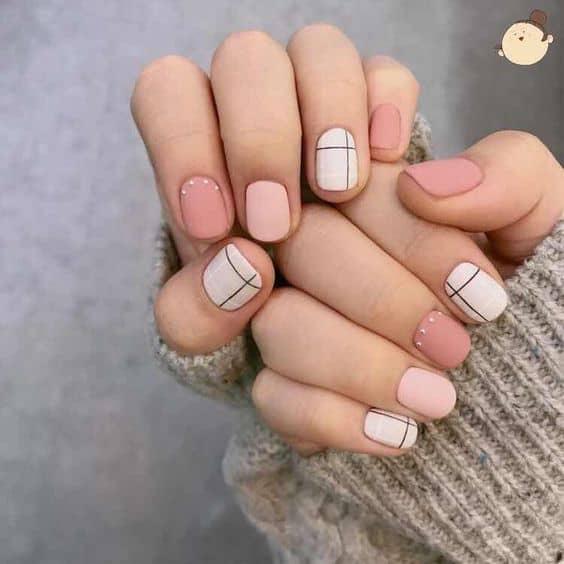 Uñas con líneas sobre fondos azules, rosas y blancas de tonos pastel.
