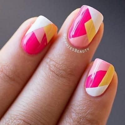 Uñas geométricas con fucsia, rosa, amarillo y blanco